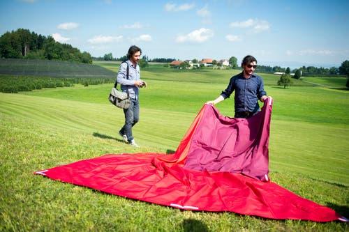Patrik (l.) und Frank Riklin breiten die Stoffbahnen aus. (Bild: Urs Bucher)