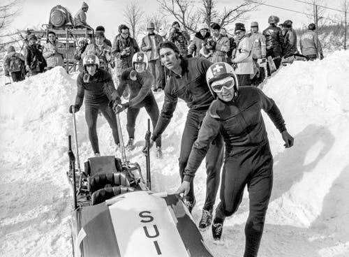 Das Team Schweiz 1 macht den Bob startklar. Jean Wicki, Edy Hubacher, Hans Leutenegger und Werner Camichel (v.l.) gewinnen Gold. (Bild: Keystone/Str)
