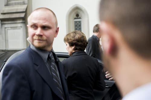 Witwe Paola Felix steigt hinter den Sicherheitsbeamten ins Auto. (Bild: Keystone)