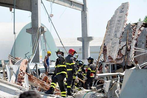 Feuerwehrleute suchen in einer kollabierten Fabrik in Mirandola nach Opfern. (Bild: Keystone / AP)