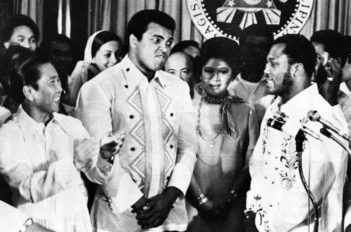Der philippinische Präsident Ferdinand Marcos (links) applaudiert während Boxer Joe Frazier (rechts) über den Schwergewichtsweltmeister Muhammad Ali (Mitte) spricht. (Bild: Keystone)