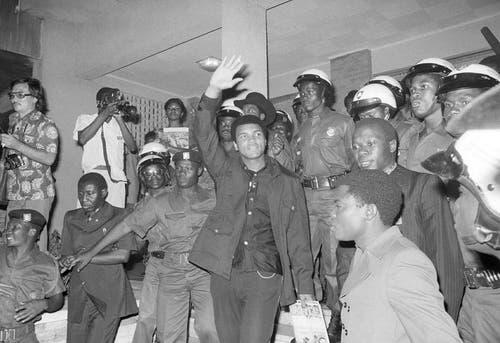 Muhammad Ali, umgeben von Soldaten, winkt in den Menschen zu, welche ihn in Kinshasa empfangen. (Bild: Keystone)