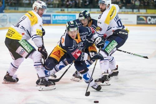 Zugs Sven Senteler enteilt den Ambri-Spielern Adam Hall und Adrien Lauper (rechts) . (Bild: Alexandra Wey / Keystone)