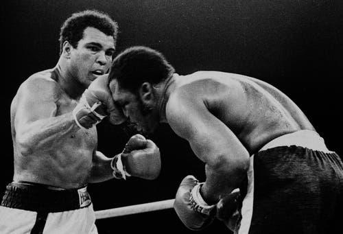 Muhammad Ali (links) landet einen Treffer geen Joe Frazier in der 13. Runde im Titelkampf in Manila auf den Philippinen im Jahr 1975. (Bild: Keystone)