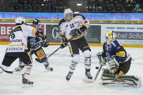Die Luganesi Thomas Rüfenacht und Mikko Lehtonen beschäftigen die Zuger Santeri Alatalo und Goalie Michael Tobler. (Bild: Keystone)