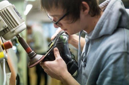 Bevor die Sohle aufgeklebt werden kann, wird der Schuh abgeschliffen. (Bild: Michel Canonica)