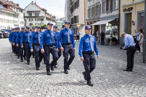 Polizeikommandant Adi Achermann führt die Schar der Aspiranten auf den Surseer Rathausplatz. (Bild: Manuela Jans-Koch, 24. Mai 2018)