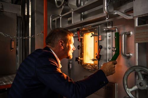 Renergia-Geschäftsleiter Ruedi Kummer blickt durch ein Fenster in den Ofen. (Bild: Roger Grütter / Perlen, 28. Mai 2018)