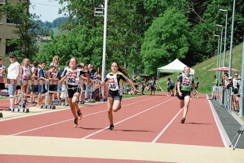 Schnell unterwegs: Elin Weber (links) und Jara Eisenring vom TV Lütisburg beim 60-Meter-Lauf. (Bild: Beat Lanzendorfer)