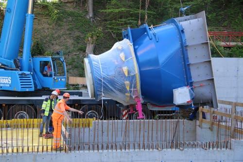 Nachdem am Grund des Rohbaus die letzten Vorbereitungsarbeiten erledigt sind, wird die 17 Tonnen schwere Turbine langsam in die Baugrube gesenkt.