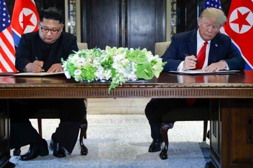 Der nordkoranische Diktator Kim Jong Un und US-Präsident Donald Trump unterzeichnen ein Dokument. Worum es sich dabei genau handelt, war bis zum Dienstagmorgen noch nicht bekannt. (Bild: AP Photo/Evan Vucci)