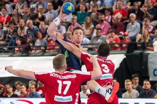 Die Schweizer Samuel Röthlisberger (links) und Lucas Meister (rechts) verteidigen gegen den Norweger Sander Sagosen. (Bild: Keystone/Alexandra Wey)