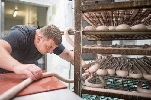 Sorgfältig legt Michael Gehringer den Schüblig auf den Räucherwagen. Im Ofen erhält die Wurst ihre klassische Farbe. (Bild: Benjamin Manser)