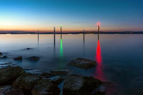 Nachts weisen farbige Signallampen an der Hafeneinfahrt in Altnau heimkehrenden Booten den Weg. (Bild: Wolfgang Reisser)