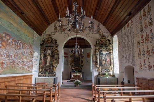 Die farbenprächtigen Wandmalereien im Innern der Schlachtkapelle. Links sieht man das Schlachtenbild und rechts die Namenslisten der gefallenen Eidgenossen sowie die Namen und Wappen der gefallenen Habsburger. (Bild: Boris Bürgisser, 18. Juni 2018)
