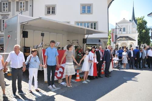 """Auf dem Dorfplatz bildeten die Sarner gemeinsam eine Menschenkette, getreu Amstads Motto """"zäme vorwärts"""""""
