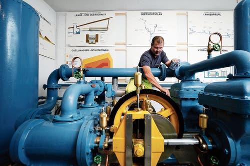 Betriebsleiter Thomas Horat mit der 100-jährigen Kolbenpumpe. (Bild: Stefan Kaiser (Baar, 6. Juni 2018))