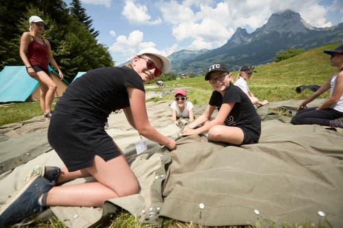 Julia Bundi, Anna Schmid und Alina Kirchhofer (von links) knüpfen die Plachen für ihr Zelt. (Bild: Jakob Ineichen, 7. Juli 2018)