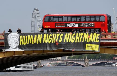 Amnesty International hat über die Vauxhall Brücke ein langes Banner mit den Worten «Der Albtraum der Menschenrechte» mit Trumps Konterfei gehisst. (Bild: AP Photo/Luca Bruno)
