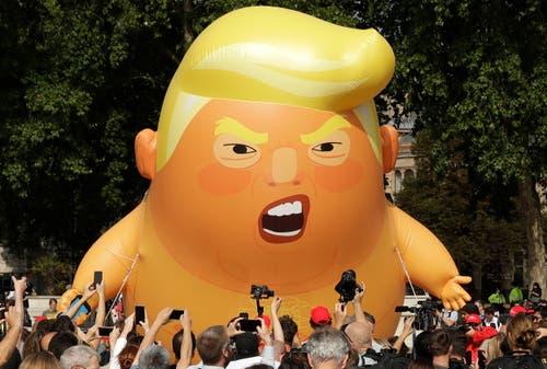 Die Demonstranten machten ihrem Unmut auch über eine sechs Meter hohe aufblasbare Trump-Figur Luft. (Bild: AP Photo/Matt Dunham)