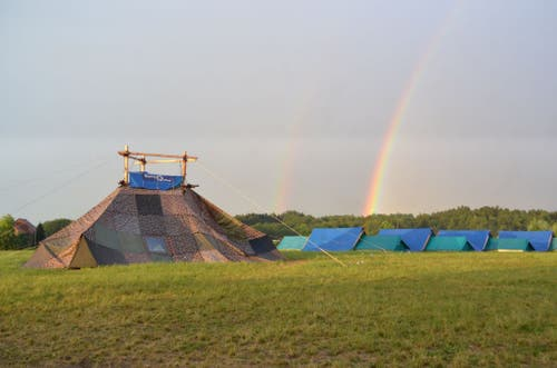 Hinter dem Sarasani-Zelt des Blaurings Willisau in Forel FR gehen zwei Regenbogen nieder. (Bild: Anja Meier)