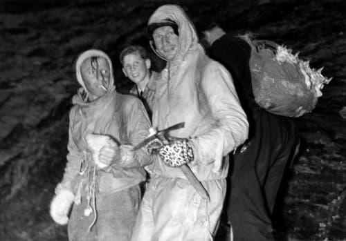 Die Erstbesteiger der Eigernordwand, Heinrich Harrer, rechts, und Fritz Kasparek, links, werden von der Münchner Alpenrettung nach ihrem Abstieg empfangen und befragt. (Bild: Keystone/ Photopress-Archiv/ Str)