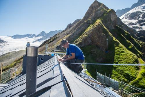 Arbeiten am Dach, mit Blick auf den Hüfigletscher (links). (Bild: Dominik Wunderli, Bristen, 18. Juli 2018)