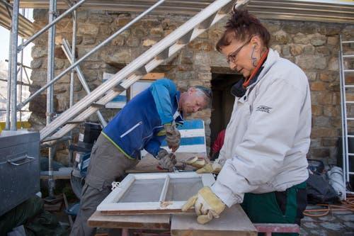 Ernst Birrer und Helena Gisler trennen Metall von den alten Fenstern. (Bild: Dominik Wunderli, Bristen, 18. Juli 2018)