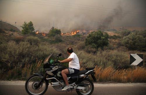Ein Motorradfahrer schaut in Kineta, westlich von Athen, auf brennende Büsche. (Bild: AP Photo/Thanassis Stavrakis (23. Juli 2018))