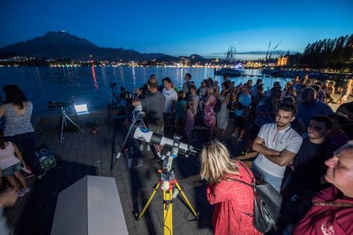 In Luzern wird das Spektakel am Vierwaldstättersee verfolgt (Bild: Urs Flüeler / Keystone)