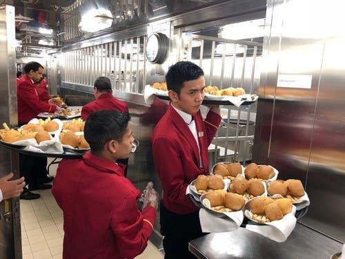 Es wird aufgetischt: Das Servicepersonal holt sich in der Küche die Brotkörbe.