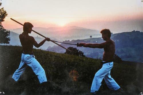 Zwei Karatemeister beim Showkampf: Peter Eigenmann mit Bo und Blacky mit Samurai-Schwert im Sonnenuntergang zwischen Wald und Heiden. (Bild: Michel Canonica/Privatarchiv Beat Cina)