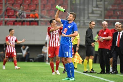 Pascal Schürpf (Luzern) erfrischt sich, während die Griechen das 3:0 bejubeln. (Bild: Martin Meienberger, Piräus, 9. August 2018)