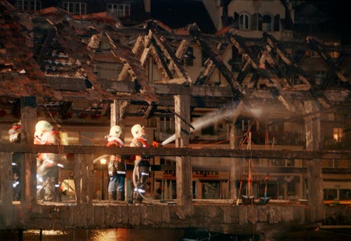 Die Feuerwehr bei den Löscharbeiten auf der Kapellbrücke . (Archivbild: Keystone/Str)