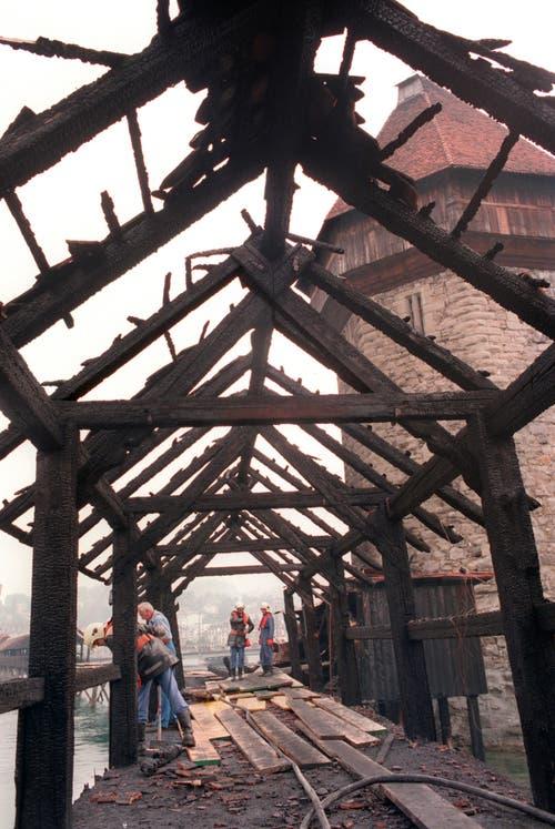 Feuerwehrleute verrichten Aufräumarbeiten nach dem Brand der Kapellbrücke. (Archivbild: Keystone/Str)