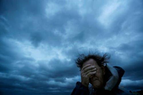 Russ Lewis schützt seine Augen vor Wind und Sand. (Bild: David Goldman/AP (Myrtle Beach, 14. September 2018))