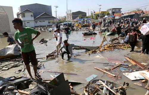 Einwohner betrachten das Ausmass der Zerstörung in Palu. (AP Photo/Tatan Syuflana)