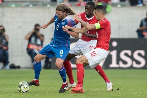 Die Schweizer Denis Zakaria (Mitte) und Granit Xhaka (rechts) kämpfen gegen Isalnds Birkir Bjarnason um den Ball. (Keystone/Peter Schneider (St. Gallen, 8. September 2018))