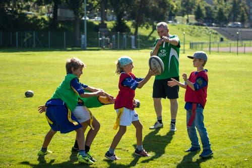Der irische Trainer des Rugby Club Luzern, Fergal O'Neill, bringt Kindern die richtige Spielweise beim Rugby bei.
