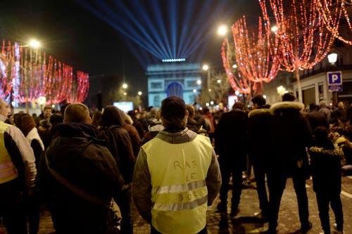 Frankreich: Der beleuchtete Triumphbogen in Paris - auch die «Gelbwesten» nutzen die Plattform für ihren Protest. (Bild: AP Photo/Kamil Zihnioglu)