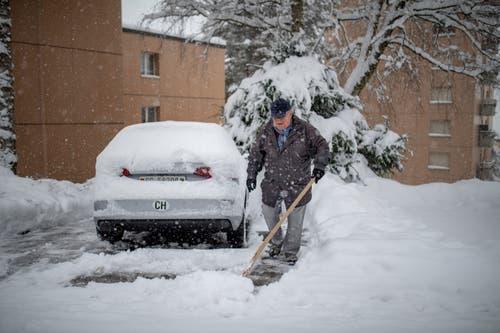 Das war am Donnerstagmorgen das Los vieler Autofahrer quer durch die Ostschweiz: Im Haggen befreit ein Autofahrer seinen Parkplatz vom Schnee. (Bild: Benjamin Manser - 10. Januar 2019)