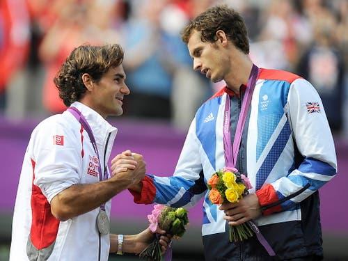 Roger Federer gratuliert Andy Murray zum Olympiasieg im Einzel. 2:6, 1:6 und 4:6 lautete im August 2012 in London das klare Verdikt im Final zu Ungunsten des Schweizers. Wenige Wochen zuvor hatte sich Federer auf dem heiligen Rasen in Wimbledon im Final gegen Murray durchgesetzt (Bild: KEYSTONE/EPA/JEAN-CHRISTOPHE BOTT)