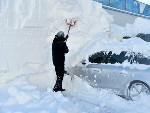Ein Mann befreit ein schwer eingeschneites Auto von der Schneelast in Obertauern (AUT). (Bild: KEYSTONE/APA/APA/BARBARA GINDL)