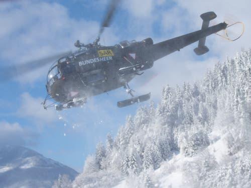 Hubschrauber der österreichischen Bundeswehr sind im Einsatz in Hall bei Admont in der Steiermark, um aus der Luft Unterstützung zu leisten und Schnee von den Bäumen zu entfernen. Im Fachjargon nennt sich das «Downwash». (Bild: KEYSTONE/APA/APA/OLIVER-JOHN PERRY)
