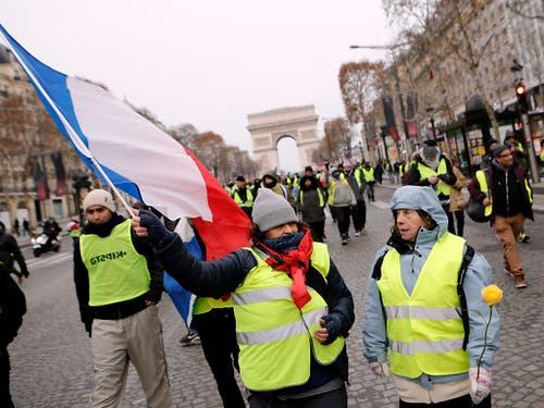 Gelbwesten beim Triumphbogen in Paris: Vor allem asiatische Touristen meiden die französische Hauptstadt im Moment wegen der Unruhen. (Bild: KEYSTONE/AP/KAMIL ZIHNIOGLU)