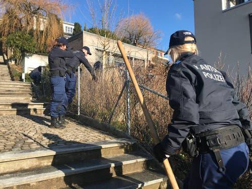 Die Polizisten suchen die Nachbargrundstücke und die Treppe zur Weinbergstrasse ab.