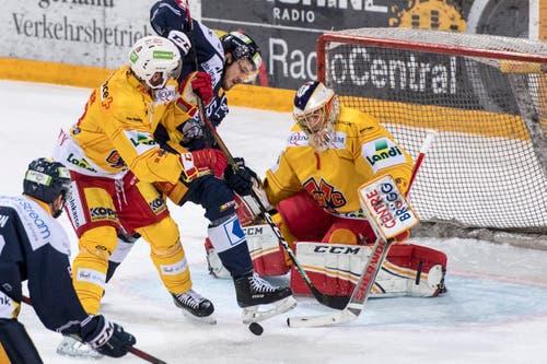 Dennis Everberg, mitte, von Zug im Spiel gegen Torhueter Jonas Hiller, rechts, in Zug. (KEYSTONE/Urs Flueeler)