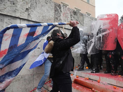 Ein Demonstrant bekämpft die Polizei mit einer griechischen Flagge. Tausende protestierten in Athen gegen den neuen Namen Nordmazedonien für den nördlichen Nachbarstaat. (Bild: Keystone/AP/Yorgos Karahalis)