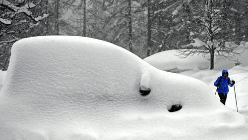 Ein eingeschneites Auto in der Ramsau am Dachstein in Österreich. Bild: Harald Schneider / APA)