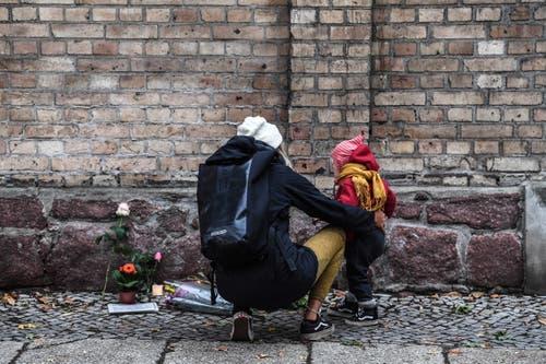 Eine Frau und ihr Kind vor den Kerzen und Blumen für die Verstorbenen in Halle. (Bild: Keystone/ Filip Singer, 10. Oktober 2019)